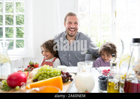 Happy father with two sons having lunch at home - Stock Photo