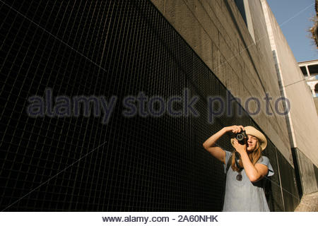 Woman taking a picture in the city, Coimbra, Portugal - Stock Photo