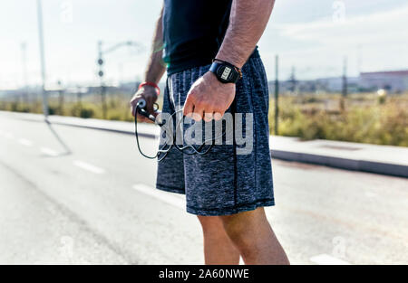 Mid section of sporty young man on a road with skipping rope