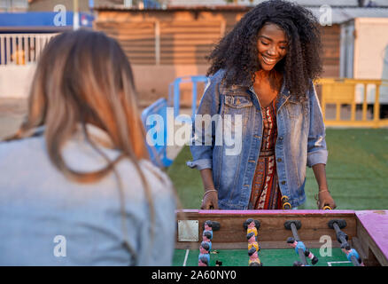 Portrait of happy young woman playing table football with her friend