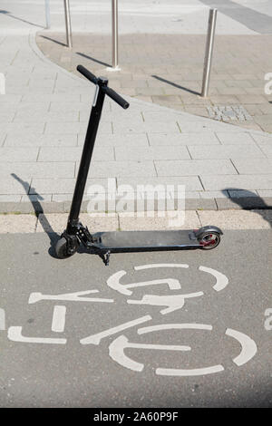 E-scooter parked on bicycle lane in the city - Stock Photo
