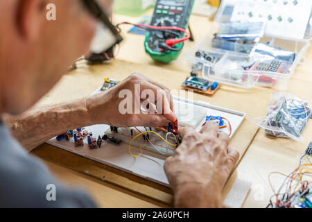 Senior man working on electronic circuits in his workshop - Stock Photo