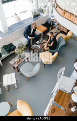 Businessman and woman having a meeting in a coffee shop, discussing work - Stock Photo