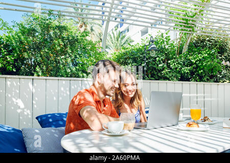 Cheerful young couple using laptop during breakfast