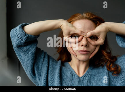 Portrait of redheaded woman shaping glasses with fingers