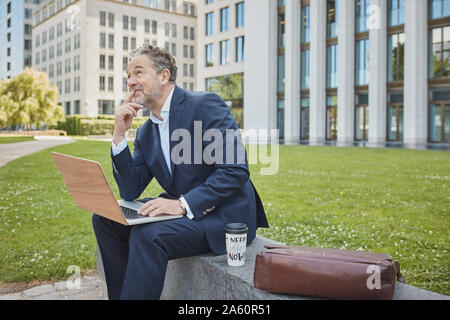 Mature businessman sitting on a wall in the city using laptop - Stock Photo