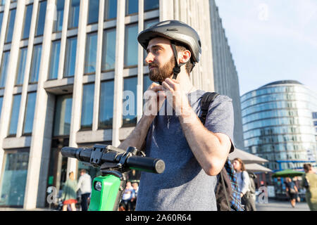 Man using e-scooter in Berlin, fastening safety helmet, Germany - Stock Photo