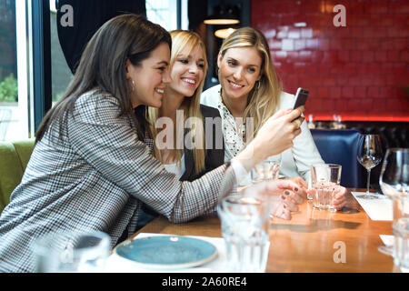 Three happy businesswomen in a restaurant looking at smartphone together - Stock Photo