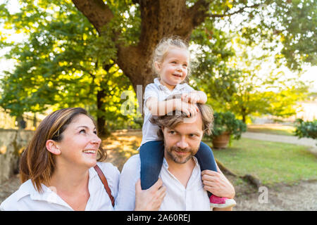 Happy family in a park with father carrying little daughter on his shoulders