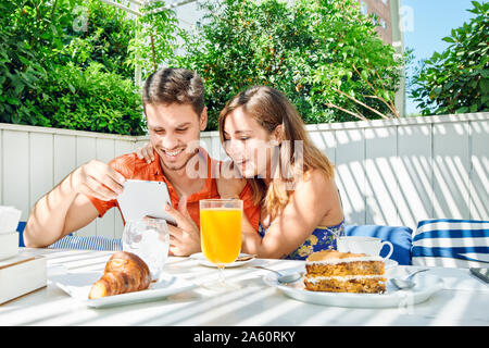 Cheerful young couple using tablet during breakfast - Stock Photo