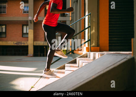 Young sportive man running upstairs on outdoor staircase - Stock Photo