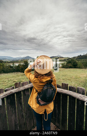 Young woman wearing yellow coat and backpack with a hand holding a hat in her head looking the lake landscape on top of a wood balcony - Stock Photo