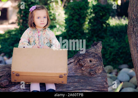 Portrait of little girl sitting on deadwood with leather suitcase - Stock Photo