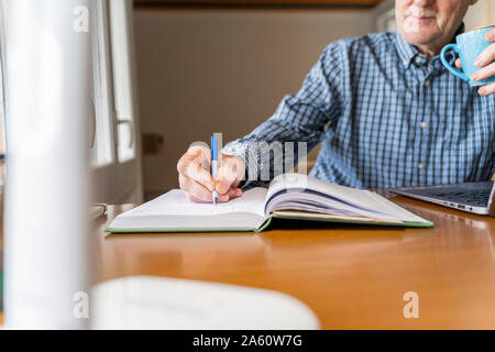 Senior man sitting at home in front of laptop making notes