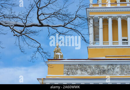 Ancient statue of a warrior-hero covered with snow framed by branches on the Admiralty building (St. Petersburg) - Stock Photo