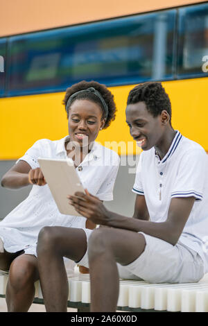 Young couple using digital tablet outdoors - Stock Photo