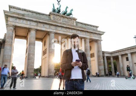 Man using smartphone in front of the Brandenburg Gate, Berlin, Germany