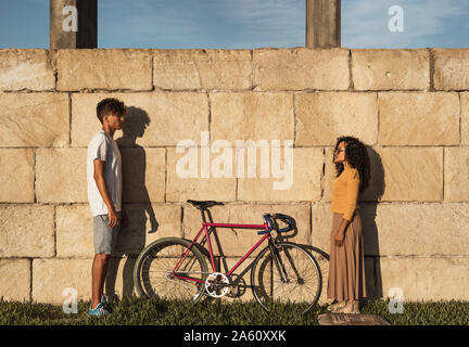 Young couple with bicycle, standing in front of wall, face to face