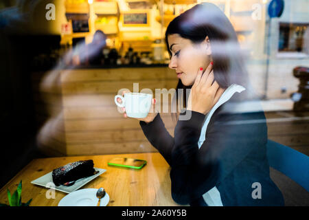Young woman in a cafe behind the windowpane - Stock Photo