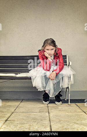 Portrait of unhappy girl wearing red leather jacket and tutu sitting on bench