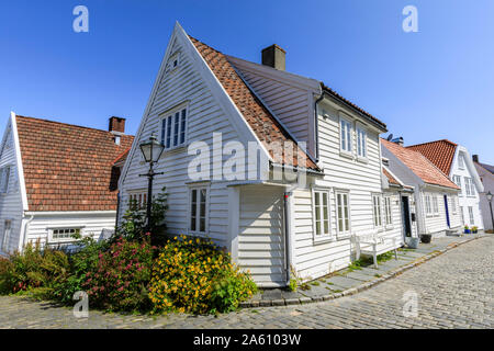 Beautiful old town, cobbled street, flowers and white wooden houses, blue sky in summer, Gamle Stavanger, Rogaland, Norway, Scandinavia, Europe - Stock Photo