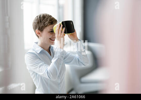 Smiling woman with VR glasses in office - Stock Photo