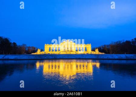 Illuminated Gloriette building mirrored in water at dusk, Schonbrunn Palace, UNESCO World Heritage Site, Vienna, Austria, Europe - Stock Photo