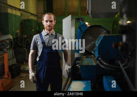 Portrait of young bearded mechanic in overalls looking at camera while standing in the factory