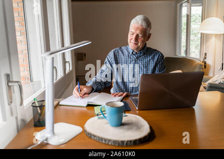 Senior man sitting at home in front of laptop making notes in notebook