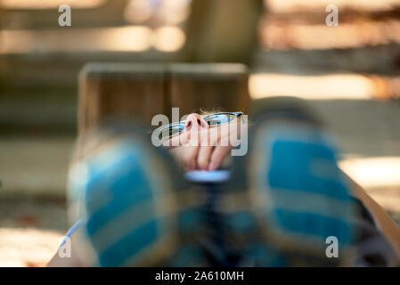 Young woman lying on park bench - Stock Photo