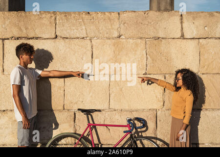 Young couple standing in front of wall, pointing at eachother - Stock Photo