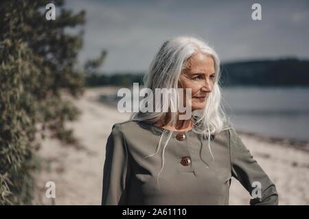 Senior woman looking at the sea, portrait - Stock Photo