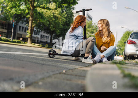 Female friends with e-scooter talking at the roadside in the city - Stock Photo