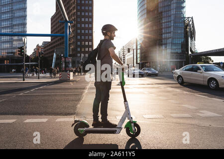Man using e-scooter in Berlin, Germany - Stock Photo