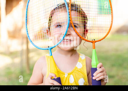 Little girl playing with colorful badminton rackets outdoors in summer