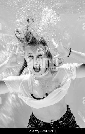 Portrait of screaming teenage girl wearing t-shirt diving under water
