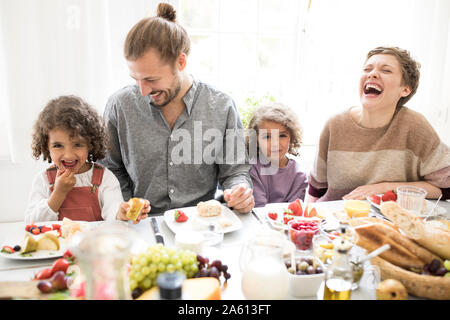 Happy family having lunch at home - Stock Photo