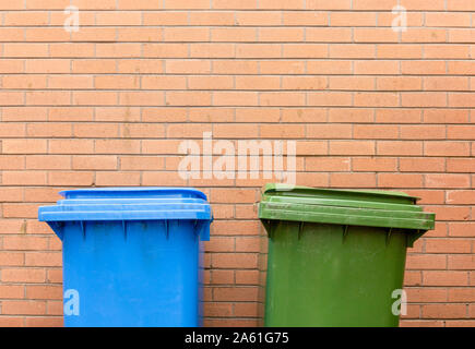 Green and Blue Recycle bins against a brick wall with space for copy - Stock Photo