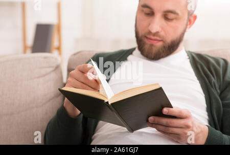 Close up of bearded man reading book at home - Stock Photo