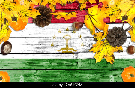Tajikistan flag on autumn wooden background with leaves and good place for your text - Stock Photo