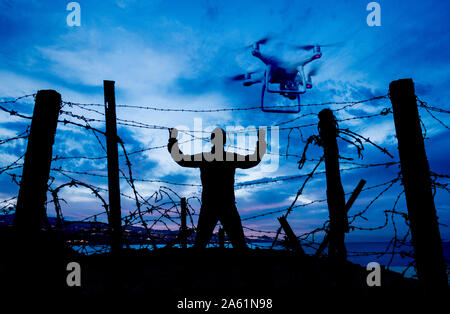 Silhouette of man looking through barbed wire fence at night with drone overhead. Brexit, immigration, asylum, technology, border control concept. - Stock Photo