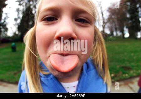 A six-year-old Caucasion girl sticking out her tongue for the camera - Stock Photo