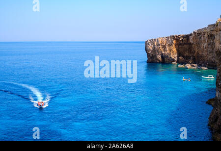 Tourists crowd at Blue Lagoon to enjoy the clear turquoise water on a sunny summer day with and boats on Comino island, Malta. - Stock Photo