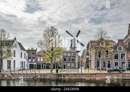 Schiedam, The Netherlands, October 23, 2019: view across the Long Harbour towards Fish Market square, with a windmill, old lanterns and houses and an - Stock Photo