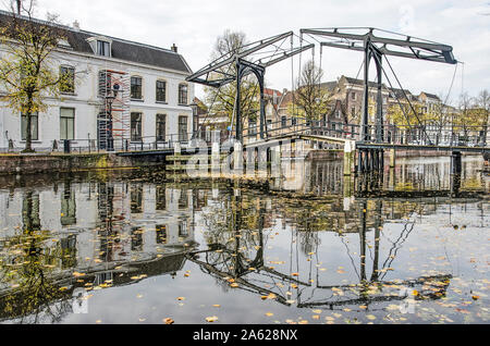 Schiedam, The Netherlands, October 23, 2019: the Apple Market bridge reflects in the calm water of the Long Harbour, dotted with fallen leaves - Stock Photo
