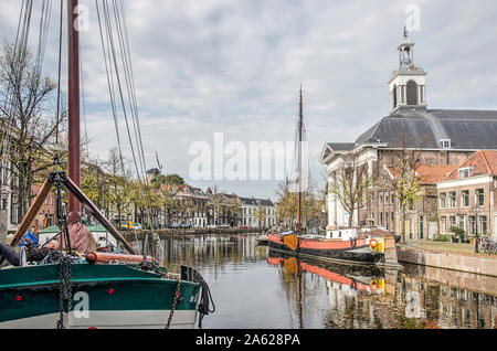Schiedam, The Netherlands, October 23, 2019: historic barges, in use as houseboats, are moored in the Long Harbour near the church of Saint John the B - Stock Photo