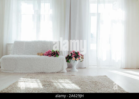 white sofa with flowers in the interior of the white room - Stock Photo