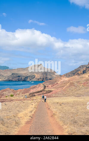 People hiking in Ponta de Sao Lourenco in Portuguese Madeira. The easternmost point of the beautiful island. Volcanic landscape, soil. Hilly, rocky terrain. Hikers on a path. Atlantic ocean coast. - Stock Photo