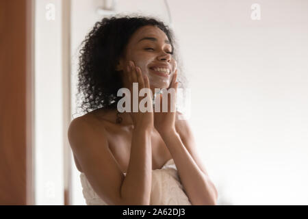 Happy african americam woman applying skincare soothing mask at bathroom. - Stock Photo
