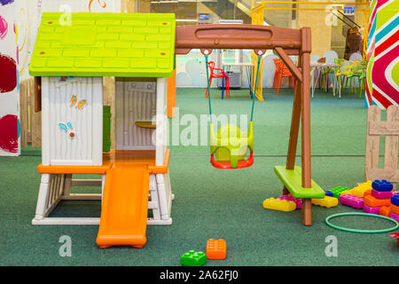 Multi-colored slide with a green mat at the bottom in the children entertainment center. Children room with many toys. - Stock Photo